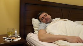 A sick young man in a bed. stock footage
