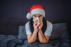 Sick young man in christmas red hat sits on bed. He is covered with blanket. Guy sneezing into tissue. He suffers. Young royalty free stock photos