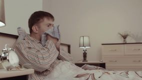 Sick young man lying in bed and sneezing stock video