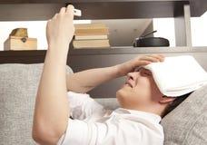 Sick young man lying on sofa checking his temperature Royalty Free Stock Photos