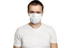 Sick young man in medical mask looking. On Stock Photography