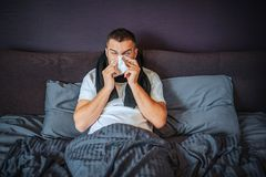 Sick young man sits on bed. He is covered with blanket. Guy sneezing into tissue. He suffers. Young man feels terrible stock images