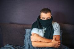 Sick young man sits on bed and coveres up his mouth with scarf. It is cold in room. Guy keeps hands crossed. He got cold. Young man suffers stock photo