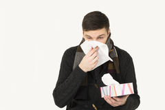 Sick young men. Portrait of a sick young man blowing her nose Royalty Free Stock Images