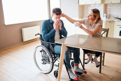 Sick young man with special needs and disability sneezing. Sick and ill guy. Young woman sit beside in kitchen and take royalty free stock image