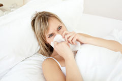 Sick young woman blowing lying on her bed Royalty Free Stock Photo