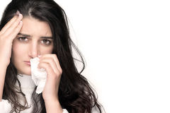 Sick Young Woman with Flu or Allergy over White Background. Portrait of beautiful brunette with headache and blows her nose into a tissue over white background Stock Photos