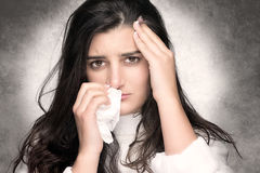 Sick Young Woman with Flu or Allergy. Portrait of beautiful brunette with headache and blows her nose into a tissue Stock Image