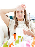 Sick young woman having fever lying on the sofa. In the living room Royalty Free Stock Image