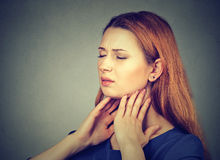 Sick young woman having pain in her throat. Closeup girl with sore throat touching her neck. Sick young woman having pain in her throat isolated on gray wall Stock Photos