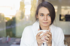 Sick young woman holding coffee mug at home Royalty Free Stock Images
