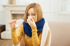 Sick young woman holding and looking at medication. Having disease. Pretty ill young blond woman having fever and blowing her nose and holding medication while Royalty Free Stock Photos