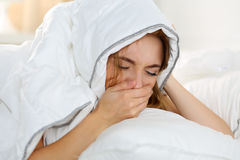Sick young woman lying in bed suffering with cold. Covering nose with hand while sneezing. Female feeling sickness and unwell hiding head under blanket Royalty Free Stock Photo