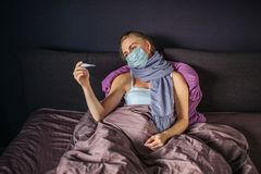 Sick young woman in mask is lying on bed and looks at thermometer. She holds it in one hand. Woman sad and upset. She is royalty free stock image