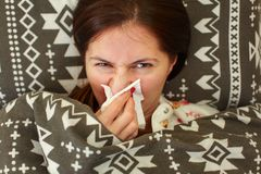 Sick young woman in pyjama, laying in bed, covered under duvet,. Holding tissue handkerchief in her hand to blow runny nose Royalty Free Stock Photos