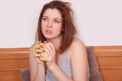 Sick young woman with red nose holding a cup of tea Stock Photography