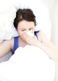 Sick young woman relaxing in her bed Royalty Free Stock Photos