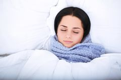 Sick young woman resting in the bed at home.  Royalty Free Stock Images