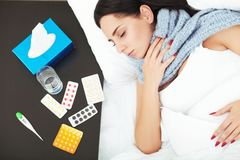 Sick young woman resting in the bed at home.  Stock Photos