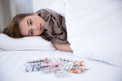 Sick young woman resting in the bed. At home Stock Photos