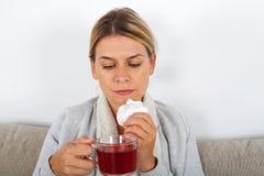 Sick woman drinking tea stock photography