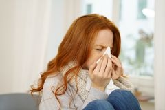Sick young woman with seasonal influenza. Blowing her nose on a tissue as she relaxes indoors at home in a close up view Royalty Free Stock Images