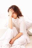 Sick young woman sitting in bed Royalty Free Stock Photo