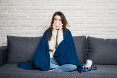 Sick young woman sitting on sofa blowing her nose at home Stock Photo