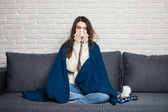 Sick young woman sitting on sofa blowing her nose at home Royalty Free Stock Image