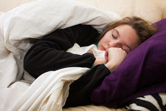 Sick young woman sleeps on couch Stock Image