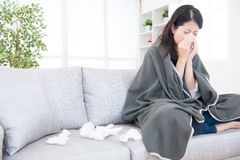 Sick young woman sneeze at home. On the sofa with a cold, she is covering with a blanket and blowing her nose. medical and health concept. mixed race asian Stock Images