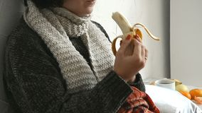 Sick young woman in the sweater lies in bed and eats a banana. At home stock footage