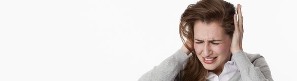 Sick young woman at tinnitus or listening to loud music Royalty Free Stock Photography