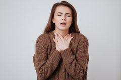 Sick young woman touching her neck. Royalty Free Stock Photos