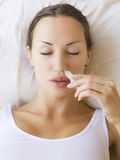 Sick young woman using ayurvedic nasal spray and laying on sofa Royalty Free Stock Photos