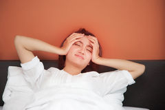 Sick young women on bed with headache, hangover, sleeplessness. Sick young woman on bed with headache, hangover and sleeplessness Royalty Free Stock Image