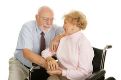 In Sickness and in Health. Loving senior couple coping with the wife's disability.  Isolated on white Stock Photos
