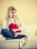 Woman being sick having flu lying on sofa Stock Photo
