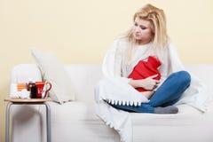 Woman being sick having flu lying on sofa. Sickness, seasonal virus problem concept. Woman being sick having flu lying on sofa hugging hot water bottle royalty free stock photography