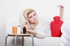 Woman being sick having flu lying on sofa Royalty Free Stock Photo