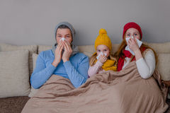 Sickness. Sneezing allergic ill family on couch Stock Images