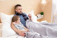 Sick daddy and daughter having a fever. Sickness. Unhealthy exhausted daddy and daughter having a cold and taking a temperature Stock Photography