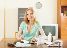 Sickness  woman counting the cost of treatment. Sickness sad woman counting the cost of treatment at home Royalty Free Stock Photo