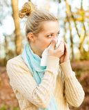 Sickness. Young beautiful woman suffering from influenza, blowing her nose Stock Photos