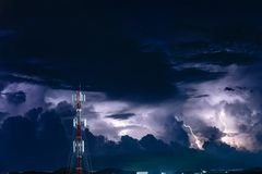 Sicksackblixtar över mobiltelefonantenntornet på natten Arkivbilder