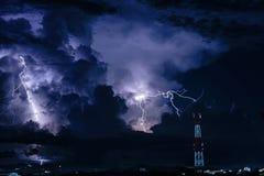 Sicksackblixtar över mobiltelefonantenntornet på natten Arkivfoto