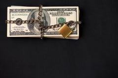 Sicuro assicuri una pila bloccata a catena di cento banconote in dollari su fondo scuro con lo spazio della copia fotografia stock libera da diritti