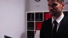 Sicuro attraente e determinato nell'uomo d'affari di auto sta camminando dentro l'edificio per uffici archivi video