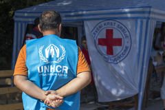 Sid,塞尔维亚- 2015年10月3日:UNHCR等待难民公共汽车的到来的职员在Berkasovo,塞尔维亚-克罗地亚边界 免版税库存图片