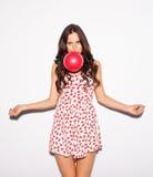 特写镜头吹一个红色气球的美丽的深色的女孩演播室画象穿短的樱桃礼服和涂她的胳膊对sid 库存图片